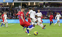 ORLANDO, FL - NOVEMBER 15: Tyler Boyd #21 of the United States sends a ball past Alphonso Davies #12 of Canada during a game between Canada and USMNT at Exploria Stadium on November 15, 2019 in Orlando, Florida.