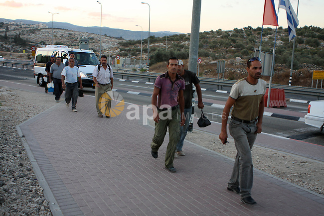 Palestinian workers walk to cross the Isreali controlled Modiin ( Bet seira )  checkpoint, between the West Bank and the Jewish settlement of Modiin Illit and all of Israeil , as they head to work in Israel and nearby settlements on October 7, 2010 . Photo by Eyad Jadallah