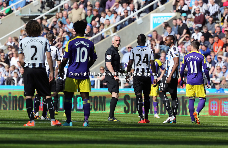 Pictured: Referee Chris Foy (C) stand up after getting knocked over by a deflection from a Jonjo Shelvey shot of Swansea. Saturday 19 April 2014<br /> Re: Barclay's Premier League, Newcastle United v Swansea City FC at St James Park, Newcastle, UK.