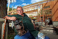 """Clyde Thomas, owner of Booneville Antiques is having his business rebuilt after it burned to the ground.  A selection of lanterns were among the few antiques salvaged from the fire, including this one on his lap.  Thomas plans to restore as many of the lanterns as he can for the store's planned re-opening.  """"I'll probably be pushing up daisies before I can finish them all,"""" he said."""