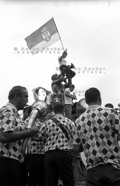 Festival di trombe e ottoni di Guca (Cacak). Gente sulla statua del trombettista, un uomo con la bandiera della Serbia e una banda che suona --- Trumpet festival of Guca (Cacak). People over the trumpeter's statue, a man with the flag of Serbia and a band playing