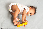 7 month old baby boy rolling on side as he grasps nubby yellow textured plastic ring full length using feet to explore toy