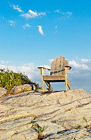 Adirondack chair sits on a rocky perch with a scenic coastal view, Newport, RI, Rhode Island