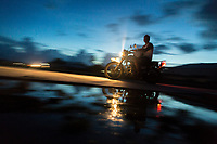 A man rides his motorbike past floodwaters in downtown Funafuti. Parts of the island flood at this time of the year due to the 'king tides'. The king tides are seasonal and are characterised by very high water levels in the surrounding ocean. At this time of year the waves inundate the coastline but also water seeps up through the ground which is made of porous coral. This natural phenomenon is particularly serious for Tuvalu, a low-lying atoll island nation, whose highest point is only a few metres above sea level. As sea levels rise, the king tides regularly flood parts of the island and will likely increase in severity in the future, potentially making large parts of the nation uninhabitable. Funafuti, Tuvalu. March, 2019.