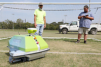 Marshall Wood (left) and Jose Hernandez, both with the city of Fayetteville's Parks and Recreation Department, monitor the robotic line painter, Turf Tank, as it is recalibrated Monday, September 14, 2020,for the correct size of soccer net on one of the fields at Kessler Mountain Regional Park in Fayetteville. The robot is currently being used to outline 42 soccer fields that are within the city at Walker, Lewis and Kessler Mountain Regional Park. Check out nwaonline.com/200915Daily/ and nwadg.com/photos for a photo gallery.<br /> (NWA Democrat-Gazette/David Gottschalk)