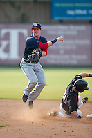 Conor Keniry (11) of the Hagerstown Suns follows through on a throw to first base as Brett Austin (20) of the Kannapolis Intimidators slides into second base at CMC-Northeast Stadium on July 19, 2015 in Kannapolis, North Carolina.  The Suns defeated the Intimidators 9-4.  (Brian Westerholt/Four Seam Images)