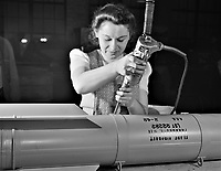 From toy trains to parachute flare casings, Stephanie Cewe has turned to the aid of Uncle Sam. She used to assemble toy locomotives; today, she uses the same screwdriver to assemble flare casings. New Haven, Connecticut, Feb 19, 1942<br /> <br /> Photo by Howard L. Hollem.