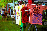Shoppers look over an assortment of t-shirts and other goods at a craft fair; Kapiolani Park, Waikiki