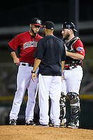 Hickory Crawdads relief pitcher Scott Williams (left) and catcher Chuck Moorman (29) listen to pitching coach Oscar Marin as he visits the mound during the game against the Charleston RiverDogs at L.P. Frans Stadium on August 25, 2015 in Hickory, North Carolina.  The Crawdads defeated the RiverDogs 7-4.  (Brian Westerholt/Four Seam Images)