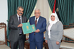 Palestinian president Mahmoud Abbas receives the annual report from a head of the administrative and financial oversight bureau, in the West Bank city of Ramallah on July 15, 2021. Photo by Thaer Ganaim