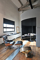 A functional, light industrial style space with exposed roof beams and a wood floor. A round table stands in a conical pod and a low cabinet rungs along one wall. A black leather and wood Eames recliner and ottoman stand in the room.