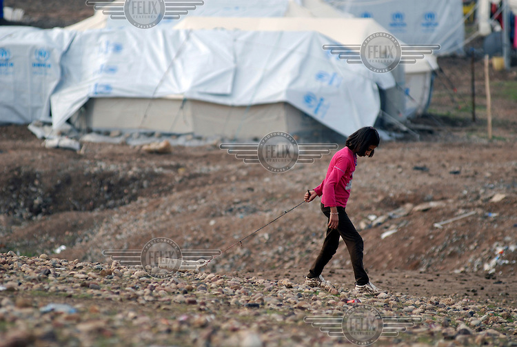 A girl gathering stones, they are used to support the tents at the Kawergosk Syrian Refugee Camp.
