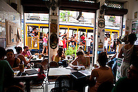 Young people drink beer at Bar do Mineiro in Santa Teresa quarter, a bohemian district in Rio de Janeiro,  Santa Teresa streetcar in background, Brazil.