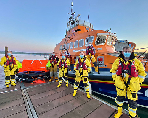 RNLI Lifeboat crewmembers under Coxswain Sean O Farrell after they arrived back, with the orange liferaft in the background