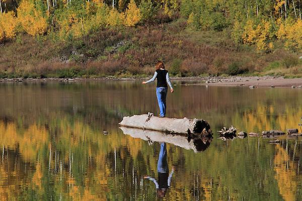 Young Caucasian woman balancing on a log in Maroon Lake, near Aspen, Colorado.