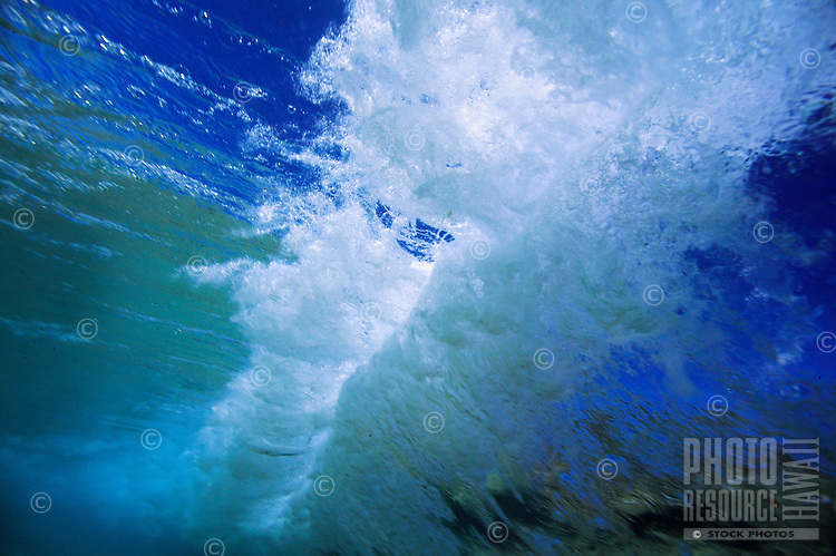 view of wave breaking from under the cool, clear, tropical ocean water