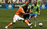Kei Kamara (l) of the Houston Dynamos attempts to fight through Tyson Wahl (c) and Peter Vagenas (r) of the Seattle Sounders in the match at the XBox Pitch at Quest Field on July 11, 2009. The Sounders defeated the Dynamo 2-1.