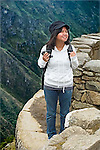 FILIPINA American FEMALE-18 YEARS-WITH BACKPACK, STANDS ON ROCK WITH MACHU PICCHU IN BACKGROUND