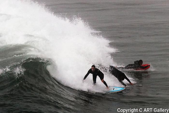 Surfer surfers surf Surfing surfboard Seal Beach California.  Photograph by Alan Mahood.
