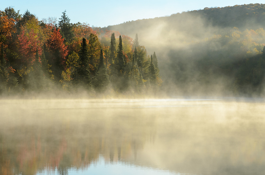 Morning fog rising on a crisp autumn morning at Lake Plumbago. Alberta, MI.