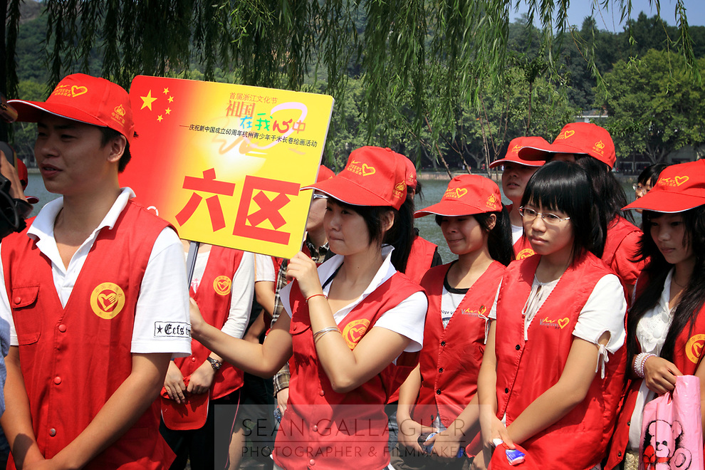 CHINA. Hangzhou. Young students volunteer to help visitors to Hangzhou in the run up to the celebrations for the 60th anniversary of the founding of the People's Republic of China.  2009