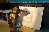 MR / Schenectady, NY. Zoller Elementary School (urban public school). Kindergarten inclusion classroom. Student (boy, 5) draws shapes by tracing a template during math learning center time. MR: Ger2. ID: AM-gKw. © Ellen B. Senisi.