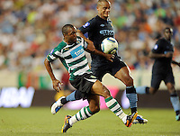 Florent Sinama-Pongolle (10) of Sporting Clube de Portugal battles Vincent Kompany (33) of Manchester City F. C. for the ball. Sporting Clube de Portugal defeated Manchester City F. C. 2-0 during a Barclays New York Challenge match at Red Bull Arena in Harrison, NJ, on July 23, 2010.