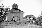 "Y-680604-B06.  Octagonal Shell gas station, known as ""The Roundhouse"" at its original location between the old hotel and the railroad tracks. It was later moved to Highway 99E, restored and declared a historic building in Aurora. Afterward, it was renamed the Octagonal building and moved again behind the Colony Store And Hall, at the intersection of Main & 2nd St. NE. Aurora, Oregon. June 4, 1968"