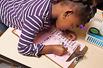 Education preschool girl signing in her name on morning sign-in sheet horizontal