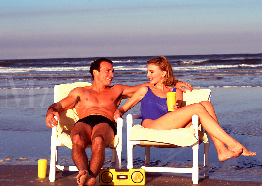 Couple relaxing in beach chairs with radio, sipping beverages