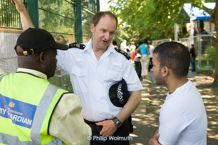 Residents, police and City Guardians at a community safety stall at Queens Park Gardens summer festival, West London.