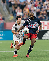 FOXBOROUGH, MA - JULY 25: Andrew Farrell #2 of New England Revolution passes the ball back as Joaquin Torres #18 of CF Montreal closes during a game between CF Montreal and New England Revolution at Gillette Stadium on July 25, 2021 in Foxborough, Massachusetts.