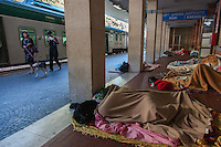 Italy. Lombardy Region. Como. Homeless african migrants sleep in the San Giovanni railway station. An italian woman walks with her dog on the platform. Her daughter is checking messages on the mobile phone. 12.08.2016 © 2016 Didier Ruef