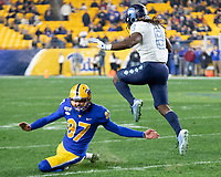 North Carolina running back Michael Carter (8) returns a kick and hurdles over Pitt kicker Alex Kessman. The Pitt Panthers defeated the North Carolina Tarheels 34-27 in overtime in the football game on November 14, 2019 at Heinz Field, Pittsburgh, Pennsylvania.