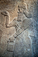 Assyrian relief sculpture panel  of a protective spirits,  from Nimrud, Iraq. The spirit is holding a symbolic fir cone and is sprinkling holy water from the bucket it is holding.   865-860 B.C North West Palace, Room G, door e, panel 1.  British Museum Assyrian  Archaeological exhibit  ref WA 124586