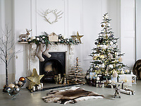 A Christmas decorated scene of a fireplace and Christmas tree.  Stockings hang from the mantelpiece and a reindeer rug lies on the floor.