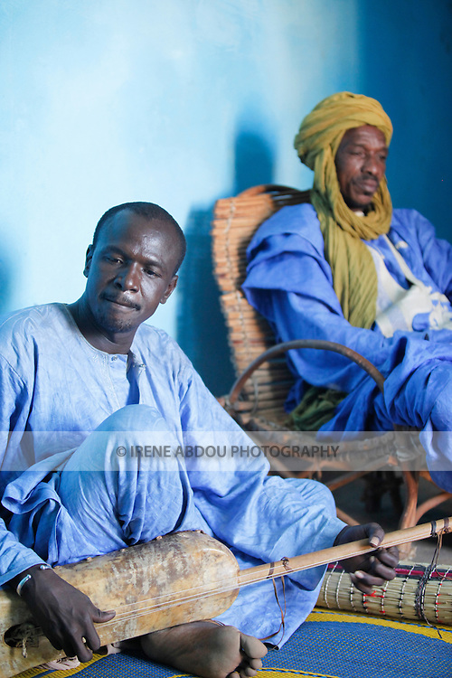 In Muslim West Africa, during the days leading up to Tabaski (Eid-Al-Adha), the griot's work grows.  Visiting families throughout the town, griots recite family histories through poetry, song, and music, refusing to leave the compound until the family pays them for their troubles.  Here, two griots, one playing a traditional guitar, call on a Fulani family in Djibo in northern Burkina Faso.