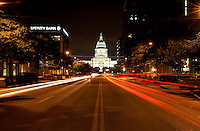Cars streak down Congress Avenue towards the majestic Texas State Capitol built 1888 of 'sunset red' pink granite from a Granite Mountain Quarry in Marble Falls - largest of all state capitols - second only in size to National Capitol in Washington DC but surpasses National Capitol in height - Austin, Texas