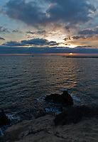 A moody sunset at Inspiration Point in Corona Del Mar.  A small sandy beach is visible in the foreground (I'm standing on a bluff above the water); the ocean is stormy / choppy, and the sunset reflects off both the scattered partial clouds and waves.