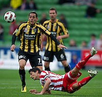 MELBOURNE, AUSTRALIA - SEPTEMBER 19, 2010: Simon Colosimo from the Heart falls to the ground as Leo Bertos watches the ball in Round 7 of the 2010 A-League between the Melbourne Heart and Wellington Phoenix at AAMI Park on September 19, 2010 in Melbourne, Australia. (Photo by Sydney Low / Asterisk Images)