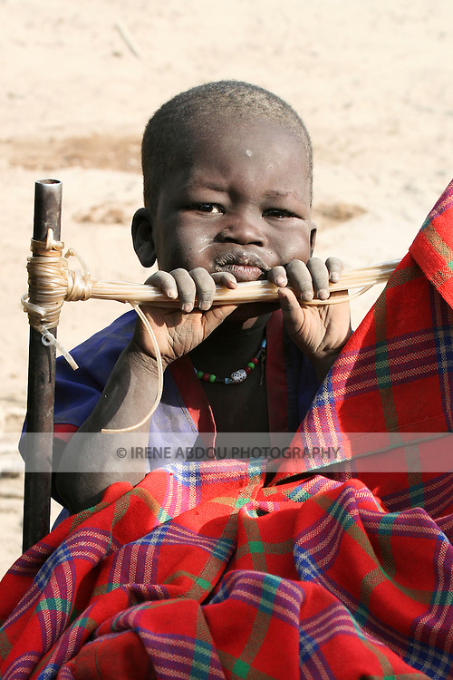 """A boy grows up in a dusty cattle camp near Akot, South Sudan.  The Dinka are traditionally """"cattle keepers,"""" living in cattle camps with hundreds or even thousands of cows."""
