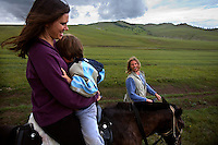 """Kristin Neff, a developmental psychologist, sits with her five-year-old autistic son, Rowan, on a horse during a horseback expedition across Mongolia. Rowan, who has been nicknamed """"The Horse Boy"""", embarked on a therapeutic journey of discovery with his parents to visit a succession of shaman healers in one of the most remote regions in the world. Following Rowan's positive response to a neighbour's horse, Betsy, and some reaction to treatment by healers, Rowan's parents hoped that the Mongolian shamanistic rituals along the route and the prolonged contact with horses would help to unlock their son's autism and assist his development.."""