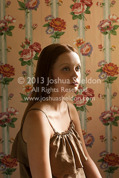 Young woman sitting in front of floral wallpaper