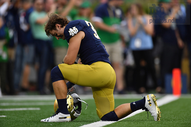 September 28, 2019; Mick Assaf kneels for a prayer before the game against Virginia. (Photo by Matt Cashore)