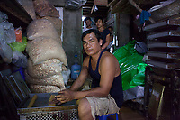 Nila's* husband Ko Kyaw Kyaw*, 44, baking cakes. They run a home-based business baking cakes and packaging dry noodles which are sold in local markets.