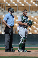 Home plate umpire Seth Buckminster and Mesa Solar Sox catcher David Freitas (70), of the Oakland Athletics organization, during an Arizona Fall League game against the Glendale Desert Dogs on October 8, 2013 at Camelback Ranch Stadium in Glendale, Arizona.  The game ended in an 8-8 tie after 11 innings.  (Mike Janes/Four Seam Images)