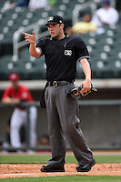 Home plate umpire Alex Ziegler signals for a gate to be closed during a game between the Tennessee Smokies and Birmingham Barons on April 21, 2014 at Regions Field in Birmingham, Alabama.  Tennessee defeated Birmingham 10-5.  (Mike Janes/Four Seam Images)