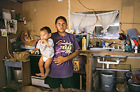 Texas, McAllen, Rio Grande Valley. Migrant mother and her baby in their home with no running water. Everyone in this area has to go to a well everyday for water.