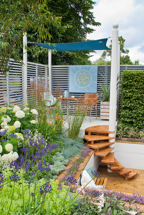 Room outdoors: Sunken deck and steps stairs with hydrangeas in bloom, lilies, thyme herbs, Persicaria, Salvia, shrubs, ornamental grasses, trees, privacy fence, levels, patio furniture, for a pretty landscaping in the backyard, creating an outdoor room