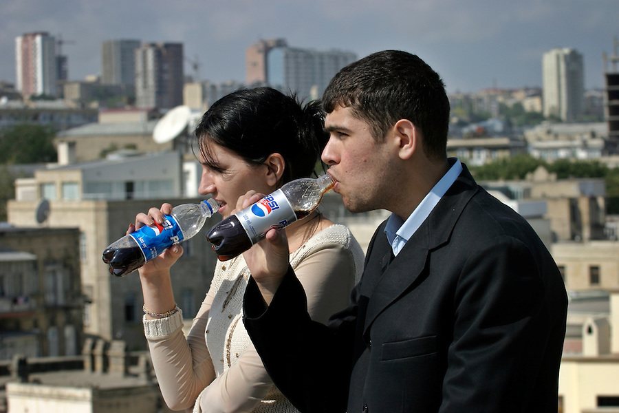 Baku, Azerbaijan, 07/10/2003..Scenes of Baku old town with new western construction projects fuelled by the regional oil boom. A young couple drink Pepsi Cola on top of the Maiden's Tower..........